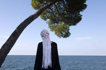Woman wearing crocheted white headdress with fringes standing in front of the sea - PSTF00687