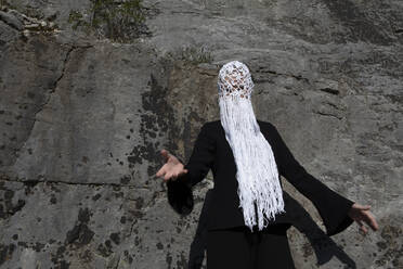 Woman wearing crocheted white headdress with fringes in front of rock face - PSTF00690