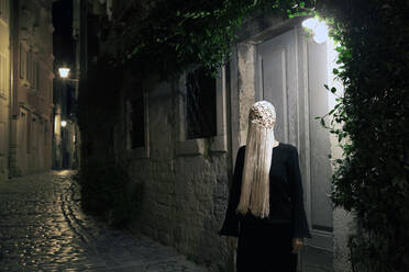 Woman dressed in black wearing crocheted white headdress with fringes at night, Rovinj, Croatia - PSTF00696