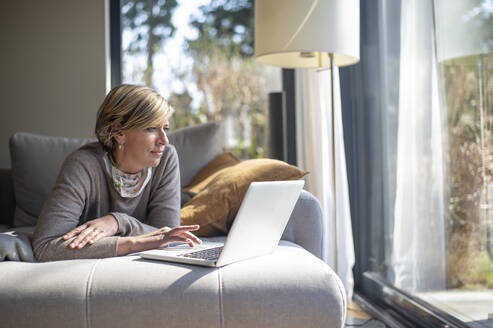 Mature woman using laptop while lying on sofa in living room during working from home - BFRF02234