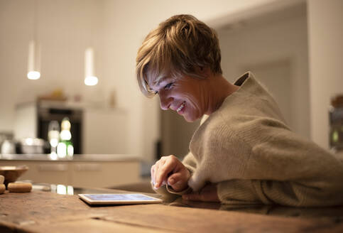 Smiling woman working late while using digital tablet in illuminated living room - BFRF02243