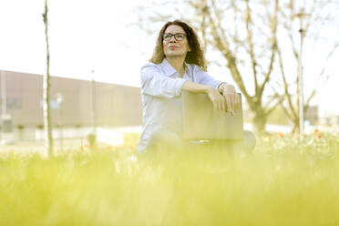 Portrait of woman with laptop sitting on a meadow looking at distance - FLLF00456