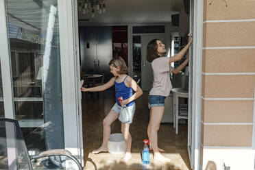 Two sisters cleaning glass panes of terrace doors - OGF00301