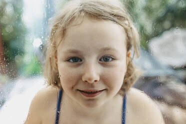 Portrait of smiling blond girl looking through wet windowpane - OGF00304