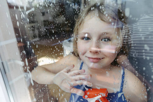 Portrait of smiling blond girl with spray bottle looking through wet window - OGF00307