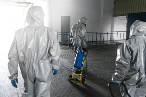 Rear view of sanitation workers walking with decontamination chemical - JCMF00664