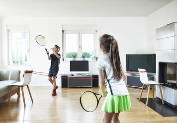 Brother and sister playing tennis at home during quarantine - DIKF00472