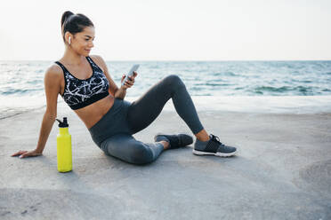 Smiling young woman using smart phone after exercising on promenade - OYF00131