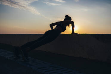 Full length of silhouette female athlete doing push-ups at promenade during sunrise - OYF00137