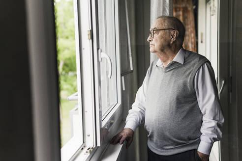 Pensive senior man looking out of window - UUF20215