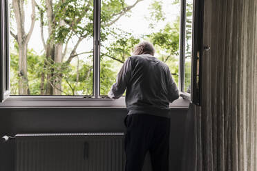 Back view of senior man looking out of window - UUF20221