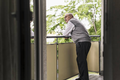 Curious senior man standing on balcony watching something - UUF20224