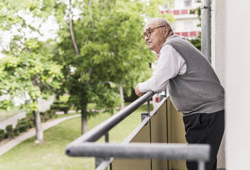 Senior man standing on balcony looking at distance - UUF20227
