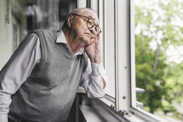 Portrait of sad senior man looking out of window - UUF20230