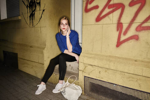 Young woman talking on mobile phone while sitting on steps at night in city - MMIF00258