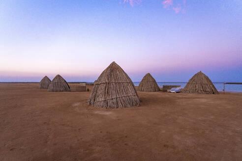 Egypt, Hurghada, Straw huts on sandy beach of Sahl Hasheesh bay at dawn - TAMF02203