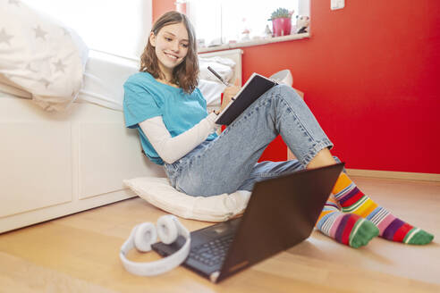 Portrait of smiling teenage girl  learning with laptop at home - STDF00218