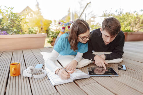 Teenage couple lying on terrace learning together with digital tablet - STDF00221