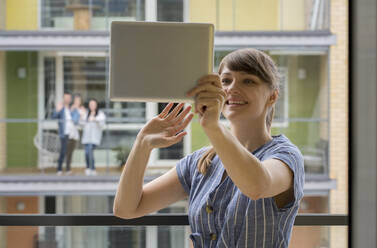 Portrait of smiling young woman using digital tablet for video chat with her neighbours - AHSF02456