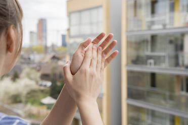 Crop view of woman clapping hands on balcony - AHSF02459