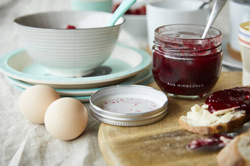 Glass of raspberry jam, bread with jam and two eggs on breakfast table - FSF01066