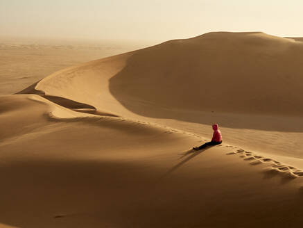 Woman sitting alone on the ridge of a dune in the desert, Walvis Bay, Namibia - VEGF02082