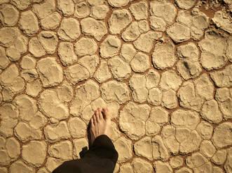 Man's foot on the cracked salt pan floor, Deadvlei, Namibia - VEGF02088