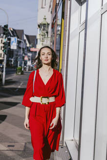 Portrait of woman in red dress walking in the city - OGF00311