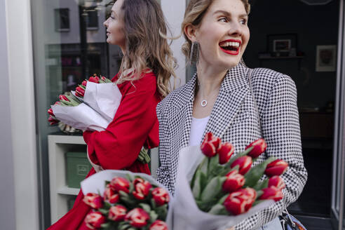 Two women leaving a flower shop with red tulips - OGF00341