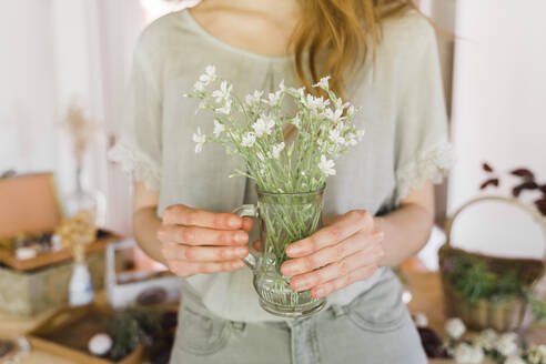 Young woman holding vase with fresh flowers - AFVF06188