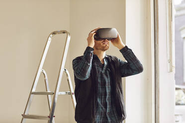 Man refurbishing shop location, using VR glasses - MCF00785