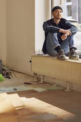 Man refurbishing shop location, sitting on windowsill - MCF00797