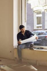 Man refurbishing shop location, sitting on windowsill, studying blueprint - MCF00800