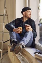 Man refurbishing shop location, sitting on windowsill, drinking coffee - MCF00806