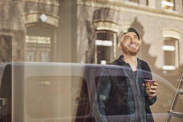 Man refurbishing shop location, drinking coffee, looking out of window - MCF00809