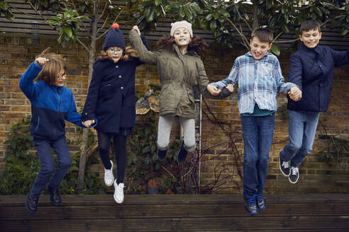 Group of children jumping on the schoolyard during break time - PWF00069