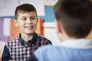Portrait of smiling boy looking at classmate in classroom - PWF00075