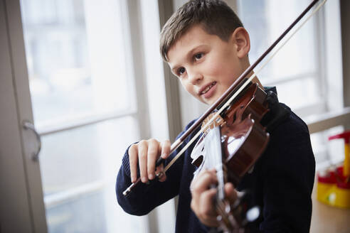 Boy playing violin during a lesson - PWF00087