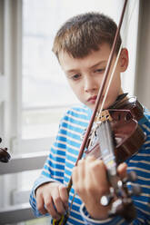 Boy playing violin during a lesson - PWF00090