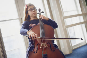 Girl playing cello during a lesson - PWF00093