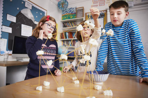 Three children setting up construction during a science lesson - PWF00102