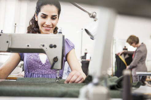 Smiling seamstress at work in a tailor shop - SDAHF00918