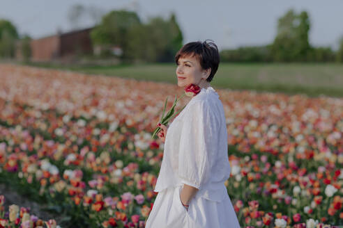 Portrait of smiling woman dressed in white standing in tulip field - OGF00362