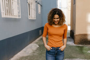 Portrait of smiling woman wearing orange pullover - TCEF00546