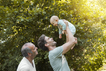 Senior man spending time with his adult son and his granddaughter in a park - DIGF10242