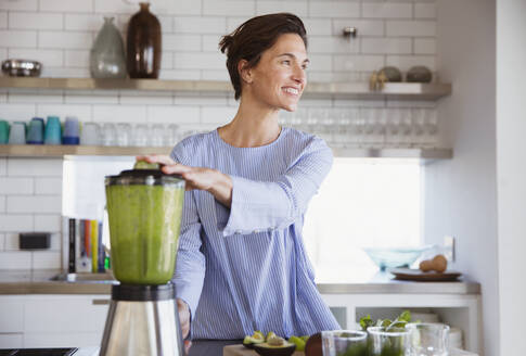 Smiling brunette woman making healthy green smoothie in blender in kitchen - CAIF26968