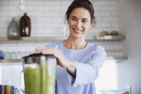 Smiling woman making healthy green smoothie in kitchen - CAIF27046