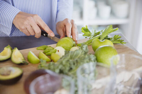 Woman cutting healthy green apples and produce on cutting board - CAIF27049