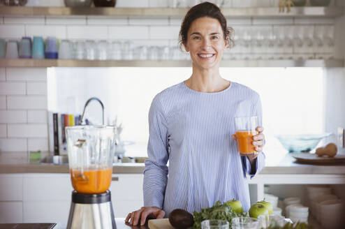 Portrait confident, smiling woman drinking healthy carrot juice in kitchen - CAIF27052