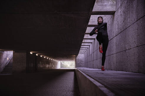Female athlete warming up before running in pedestrian underpass - DHEF00172